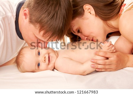 Happy family concept. Parents kissing the kid, the baby smiling. Isolated on white background.