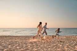 Happy family concept. Young attractive mother, handsome father and their little cute daughter having fun together on the beach and running with dog.