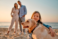 Happy family concept. Young attractive mother, handsome father and their little cute daughter standing together on the beach with dog.