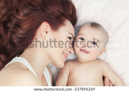 Happy family concept. Young mother and her baby smiling and hugging over white blanket.