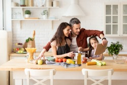 Happy family cooking together at home kitchen. Smiling mother, father and little daughter using cookbook to make dinner from fresh healthy ingredient products. Loving relationships and happiness