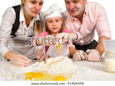 Happy family cooking  together in the kitchen while little girl adding eggs in the flour