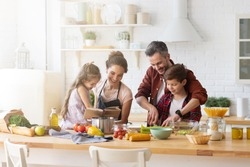 Happy family cooking together on kitchen. Mother and daughter reading recipe to father and son. Dad and boy chopping green vegetable leaf for salad. Home recreation and food preparation on weekend