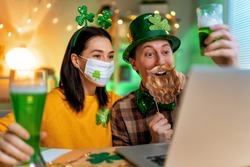 Happy family couple celebrating St. Patrick's Day with their friends by online at home.