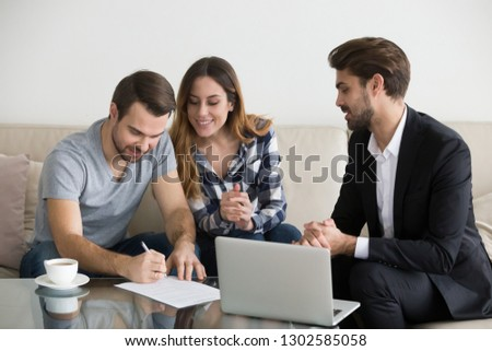 Happy family couple customers renters tenants sign mortgage loan investment agreement or rental sale purchase contract meeting realtor lender or landlord making real estate ownership deal concept