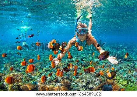 Happy family - couple in snorkeling masks dive deep underwater with tropical fishes in coral reef sea pool. Travel lifestyle, outdoor water sport adventure, swimming lessons on summer beach vacation