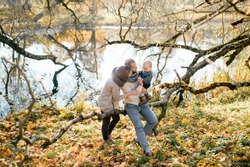 Happy family couple with their little child in autumn park in sunny day.