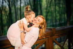 Happy family. Cute daughter kisses her mother while sitting at the bridge banister