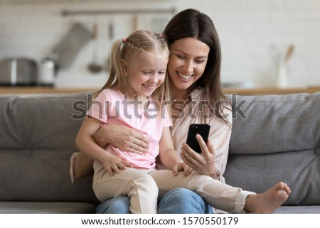 Happy family cute small kid child daughter sit on parent mom lap on sofa laugh having fun hold using smart phone watch funny social media video app take selfie bonding look at mobile screen at home