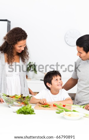 Happy family cutting vegetables together in the kitchen at home
