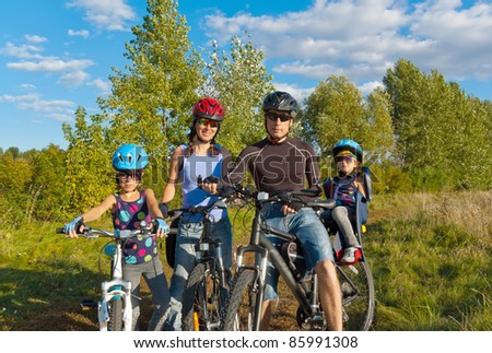 Happy family cycling outdoors. Parents with two kids on bikes