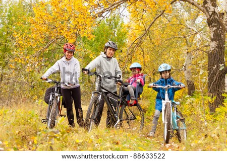 Happy family cycling outdoors, smiling parents with kids on bicycles, golden autumn in park