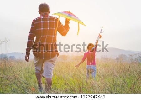 happy family dad and child run on meadow with a kite in the summer on the nature.vintage style. #1022947660