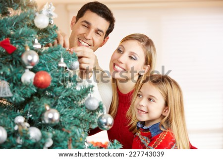 Happy family decorating christmas tree together at home