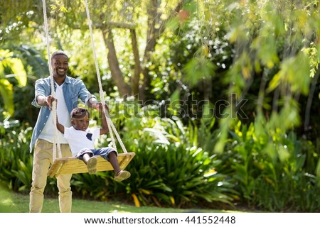 Happy family doing swing at park