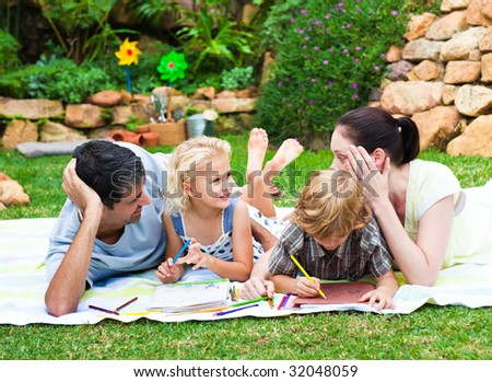 Happy family drawing together in a park