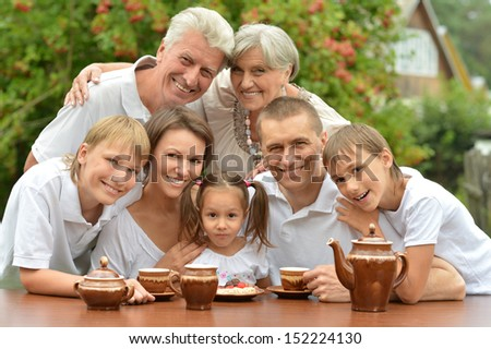 Happy family drinking tea at table outdoors in summer time