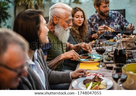 Happy family eating at barbecue home party dinner - Different age of people having fun at bbq meal in villa backyard - Summer lifestyle and food concept - Main focus on hipster man's face Stock fotó ©