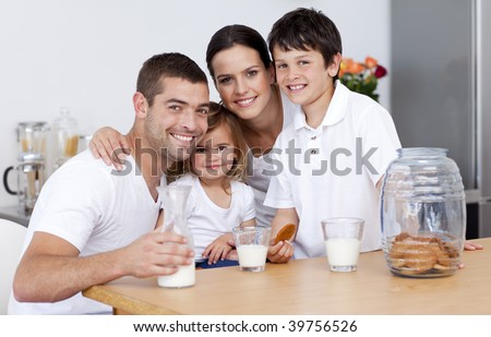 Happy family eating biscuits and drinking milk in the kitchen