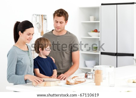 Happy family eating bread in the kitchen at home