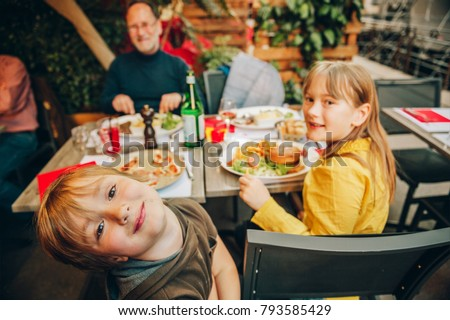 Happy family eating hamburger with french fries and pizza in outdoor restaurant