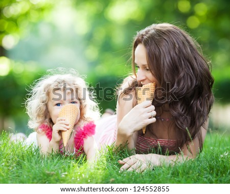 Happy family eating ice-cream outdoors in spring park against blurred green background