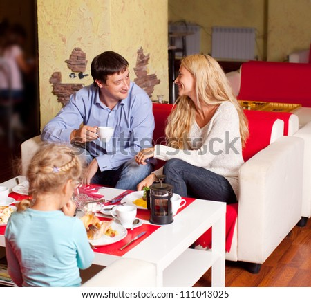 Happy family eating in cafe
