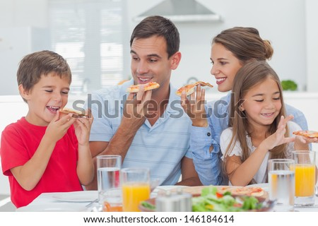 Happy family eating pizza slices for the dinner