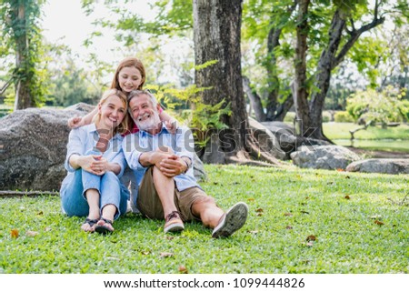 Happy family elderly caucasian and child caucasian sitting on lawn relax in weekend holiday lifestyle park outdoor nature background. #1099444826