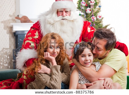 Happy family embracing and sitting on the floor in front of Christmas gifts and tree wit Natural Santa Claus