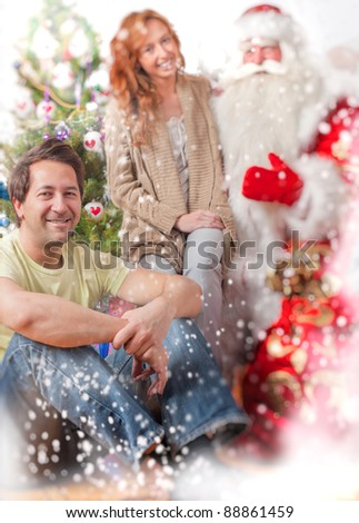 Happy family embracing and sitting on the floor in front of Christmas gifts and tree wit Natural Santa Claus. Indoors. Magic snowy poster - stock photo