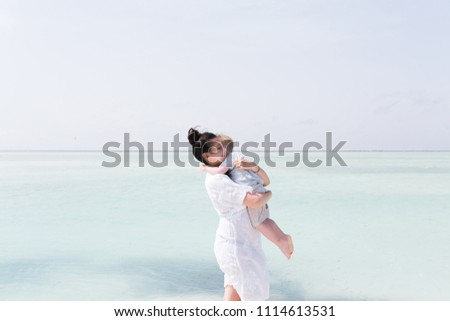 Happy family embracing at beach in summer near blue sea. Mother and toddler boy hugging and kissing together