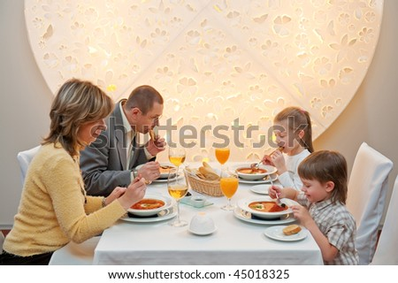 Happy family enjoying meal sitting at restaurant table