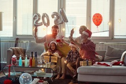 Happy family enjoying New Year eve in home festive atmosphere together. New Year, holiday, family time together