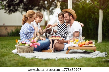 Happy family enjoying summer together at backyard and eat pie.