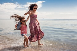 Happy family enjoying sunny day at the beach. Mother and daughter