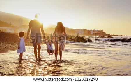 Happy family enjoying sunset in the summer leisure