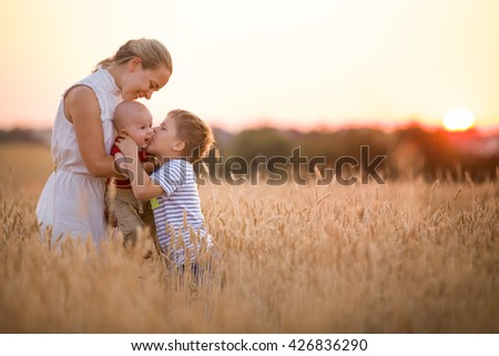 Happy family enjoying sunset in wheat field. Beautiful young woman with adorable baby boy and kid. Mother hugging her two children on a meadow on a sunny evening. Mom and sons. Outdoors.
