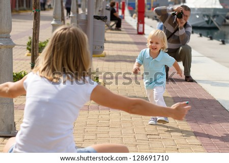 Happy family enjoying their weekend in the park in a bright summer day. Mom & son having fun, while their dad is taking photos with his DSLR camera