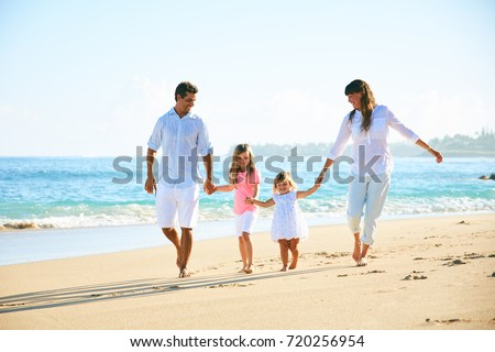 Happy family enjoying walk on the beach