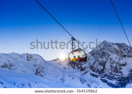 Happy family enjoying winter vacations in mountains. Father with teenage daughter going up with ski lift in Solda, South Tirol, Italy