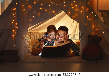 happy family father and child daughter  reading a book with a flashlight in a tent at home #583772842