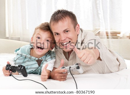 Happy family - father and child playing a video game