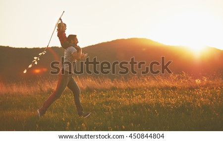 happy family father and child run on meadow with a kite in the summer on the nature #450844804