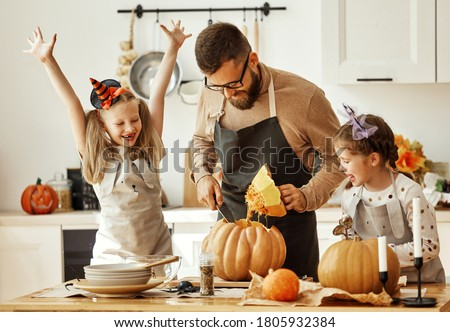 happy family   father  and children daughters prepare for Halloween by carving pumpkins at home in the kitchen