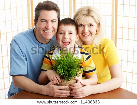 Happy family. Father, mother and boy with plant.