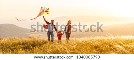 Happy family father,  mother and child daughter launch a kite on nature at sunset #1040085790