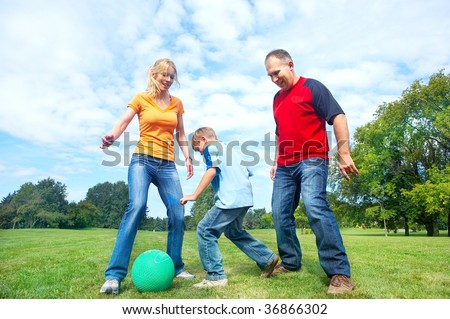 Happy family. Father, mother and sons playing football  in the park