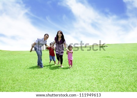 Happy family: Father, Mother, and their children. Shot outdoor in summer day