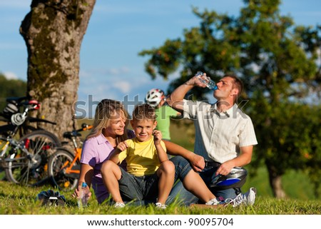 Happy family (father, mother and two sons) on getaway with bikes - they have a break